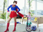 Daughter of superhero vacuuming her cape in living room - CAIF13946