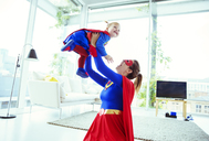 Superhero playing with baby in living room - CAIF13949