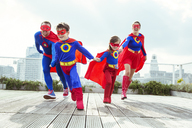 Superhero family playing on city rooftop - CAIF13961