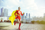 Superhero running on city rooftop - CAIF13964