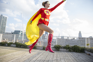 Superhero jumping on city rooftop - CAIF13967