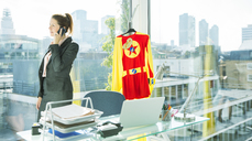 Businesswoman talking on cell phone with superhero costume behind her - CAIF13973