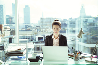 Businesswoman working on laptop in office - CAIF13976