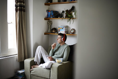 Man sitting in armchair with headphones looking through window - CAIF13979