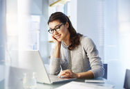 Female office worker sitting at desk using laptop - CAIF13997