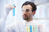 Man in laboratory looking at vial with blue fluid - CAIF14000
