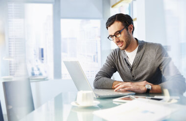 Man working using laptop in office - CAIF14018