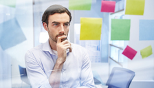 Office worker behind glass with colorful sticky notes thinking - CAIF14033