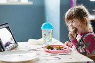 Girl eating hamburger and watching digital tablet - CAIF14036