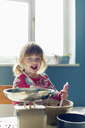 Smiling girl baking with mixing bowl in kitchen - CAIF14039