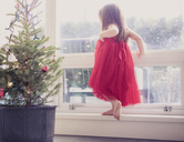 Girl in red dress on ledge next to potted Christmas tree - CAIF14051