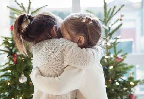 Girls hugging in front of Christmas trees - CAIF14054