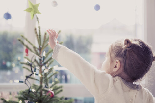 Girl reaching for start on Christmas tree - CAIF14060