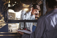 Mechanic and customer talking on cell phone under car - CAIF14066