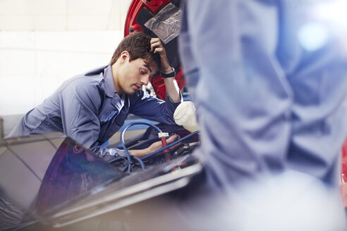 Frustrated mechanic looking down at engine in auto repair shop - CAIF14072