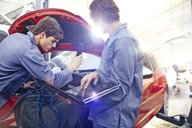 Mechanics with laptop working on car engine in auto repair shop - CAIF14075