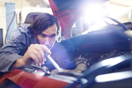 Mechanic working on engine in auto repair shop - CAIF14078