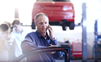 Man talking on cell phone in auto repair shop - CAIF14084