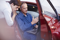 Mechanics with laptop at car in auto repair shop - CAIF14087