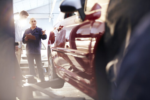 Mechanic with clipboard talking to customer in auto repair shop - CAIF14093