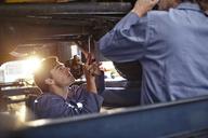 Mechanics working under car in auto repair shop - CAIF14096