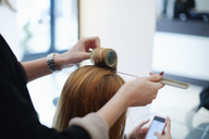 Hairdresser wrapping customer's hair in curlers in salon - CAIF14099