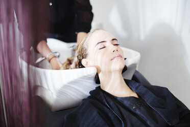 Customer with eyes closed getting hair washed in salon - CAIF14102