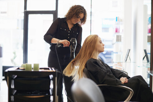 Hairdresser drying customer's long hair in salon - CAIF14105