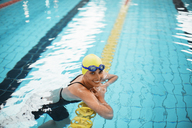 Portrait of smiling swimmer leaning on swimming lane marker in pool - CAIF14117