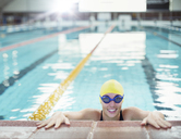Portrait of smiling swimmer at edge of pool - CAIF14123