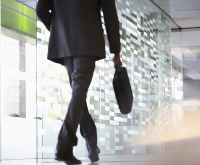 Businessman with briefcase walking in lobby - CAIF14192