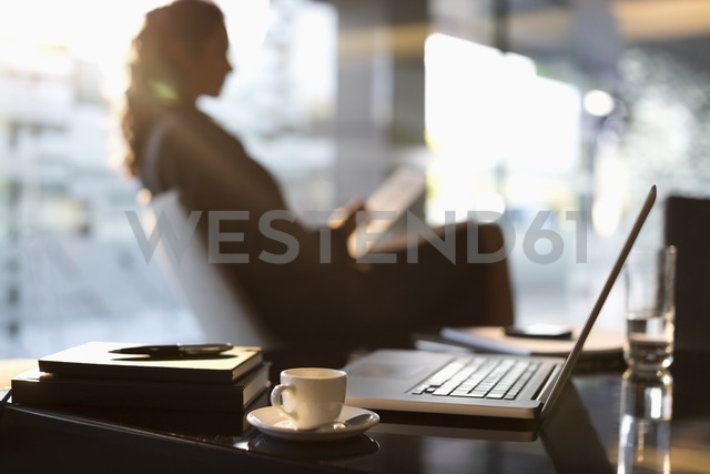Businesswoman using digital tablet in lobby - CAIF14201