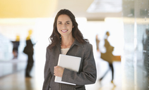 Portrait of smiling businesswoman holding digital tablet in lobby - CAIF14231