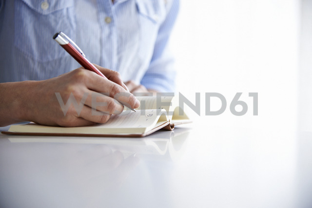 Woman writing in notebook - CAIF14264
