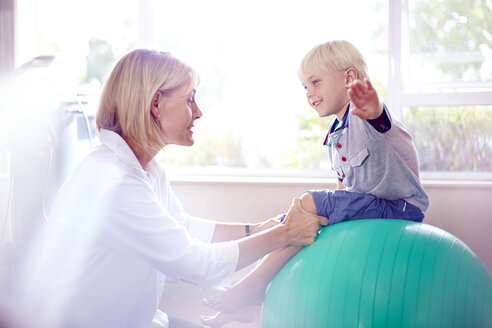 Physical therapist holding boy with arms outstretched on fitness ball - CAIF14297