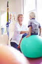 Physical therapist holding boy on fitness ball - CAIF14303