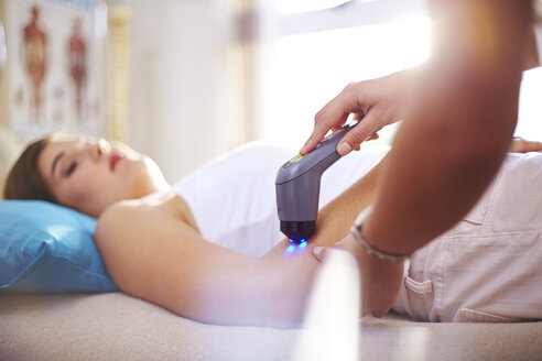 Physical therapist using ultrasound probe on woman's arm - CAIF14306