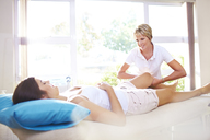 Masseuse massaging woman's leg - CAIF14309