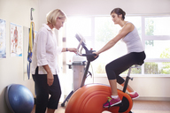 Physical therapist guiding woman on stationary bike - CAIF14324