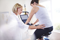 Physical therapist guiding woman's hips on stationary bike - CAIF14327