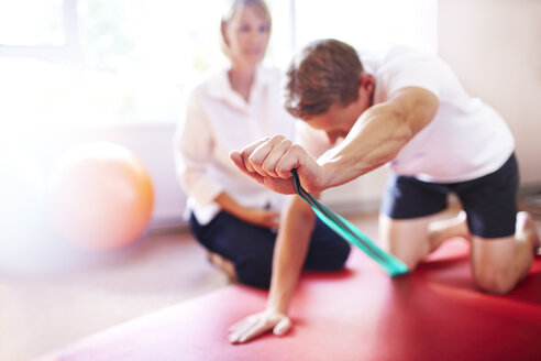 Physical therapist guiding man pulling resistance band - CAIF14330