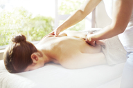 Masseuse massaging woman's back - CAIF14348