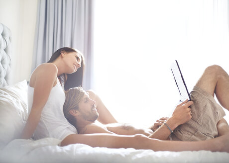 Casual couple relaxing with laptop on bed - CAIF14381