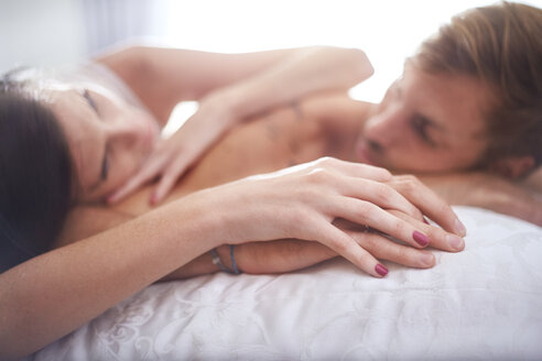 Affectionate couple holding hands laying on bed - CAIF14387