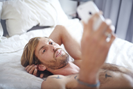 Man with bare chest laying on bed texting with cell phone - CAIF14390