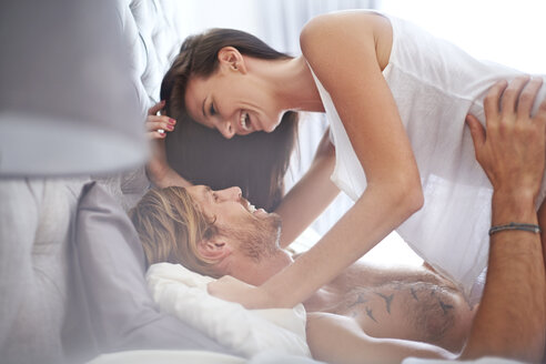 Playful couple on bed - CAIF14393