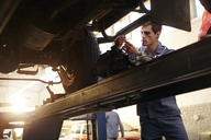 Mechanic working under car in auto repair shop - CAIF14435