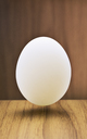 Close up of egg hovering over counter - CAIF14495