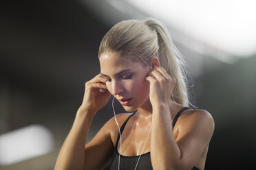 Woman exercising and listening to headphones - CAIF14498