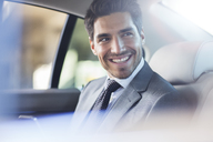 Smiling businessman sitting in car - CAIF14528
